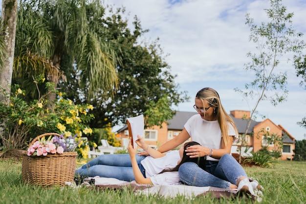 Портрет матери и дочери, наслаждаясь пикником в парке.