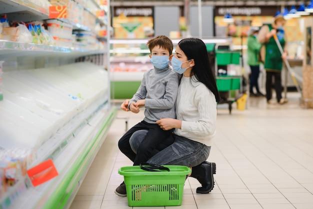 コロナウイルスの流行またはインフルエンザの流行中にスーパーマーケットで保護フェイスマスクを着用している母親と彼女の幼い息子の肖像画。テキスト用の空のスペース。