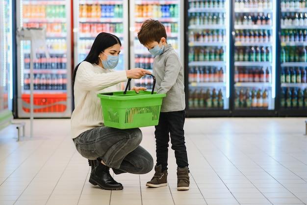 Портрет матери и ее маленького сына в защитной маске в супермаркете во время эпидемии коронавируса или вспышки гриппа. пустое место для текста.
