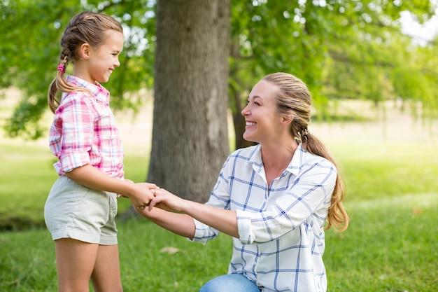公園で彼女の娘の手を繋いでいる母親の肖像画