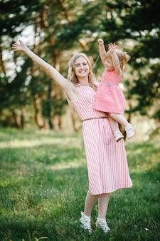 Портрет матери держит дочь на руках на природе на летних каникулах. мама и девочка играют в парке во время заката. понятие дружной семьи. закройте вверх.