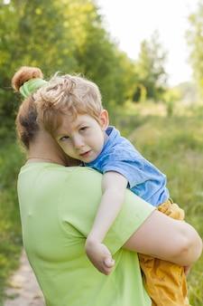 Портрет матери, обнимающей своего маленького сына с особыми потребностями в летнем парке. инвалидность. детский паралич. летние прогулки на свежем воздухе.