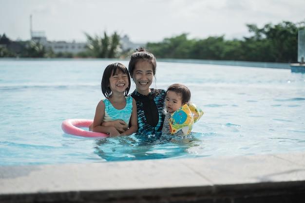 晴れた日にプールで泳ぐように子供に教える母親の肖像画