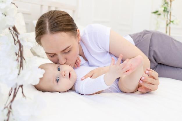 아기가있는 어머니의 초상화, 어머니는 아이에게 키스하고 집에서 흰색 침대, 모성애와 관심에 부드럽게 그를 안아줍니다.