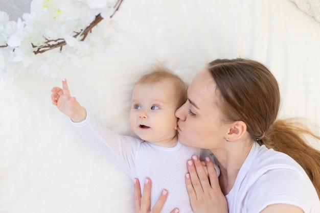 Портрет матери с младенцем, мать целует ребенка и нежно обнимает его на белой кровати дома, материнская любовь и забота.