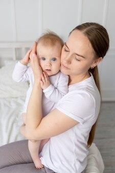 아기를 안고 집에 있는 하얀 침대에서 아기를 부드럽게 껴안고 있는 어머니의 초상화, 어머니의 사랑
