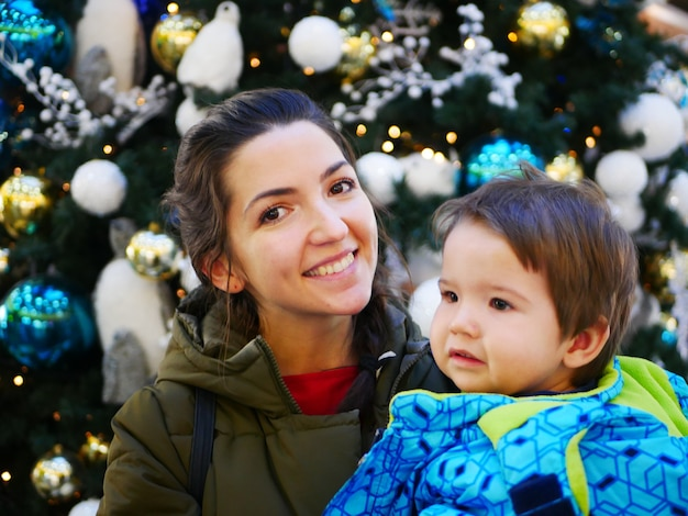 따뜻한 옷을 입고 새해 나무 근처에 아이를 둔 어머니의 초상화. 고품질 사진