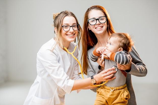 白いオフィスのインテリアに立っている彼女の男の子と小児科医と母親の肖像画