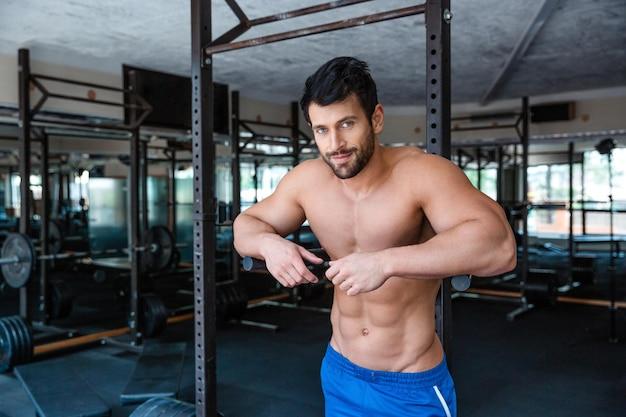 Портрет мускулистого мужчины-культуриста, отдыхающего возле брусьев в фитнес-зале