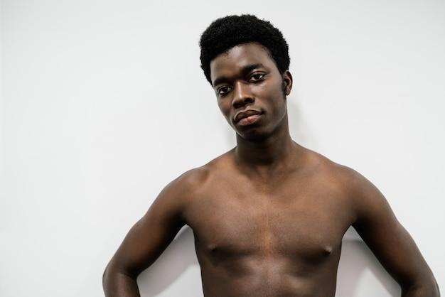 Портрет мускулистого африканского мужчины, позирующего в фотостудии на белом обнаженном фоне без футболки