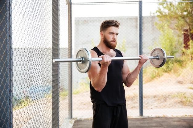 Портрет мускулистого фитнес-мужчины, делающего тяжелые упражнения со штангой на открытом воздухе