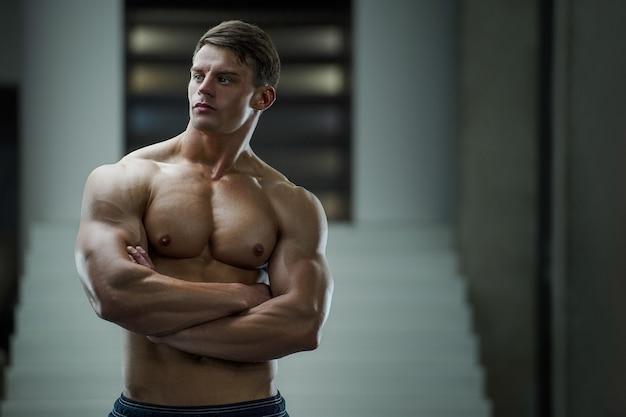 Портрет мускулистого мужчины в тренажерном зале