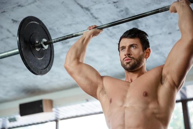 피트니스 gm에서 바벨과 근육 남자 운동의 초상화