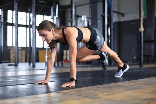 Портрет мускулистой женщины, делающей доски на полу спортзала.