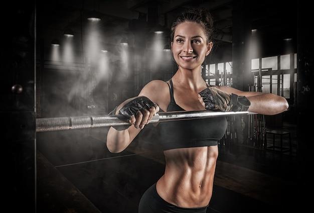 バーベルとパワーラックの近くの筋肉質の女性の肖像画。
