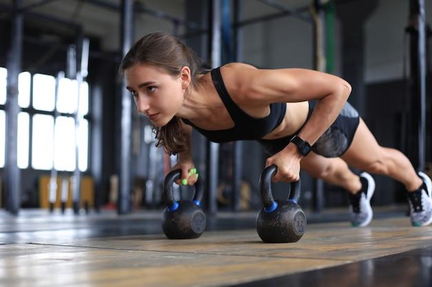 Портрет мускулистой женщины на доске с гирями в тренажерном зале.
