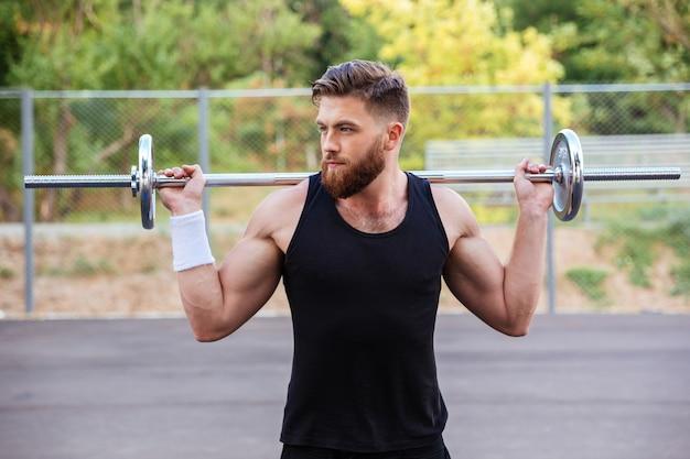 Портрет мускулистого молодого бородатого мужчины тренировки со штангой на открытом воздухе