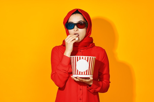 Портрет мусульманской девушки в ярком хиджабе с попкорном в очках