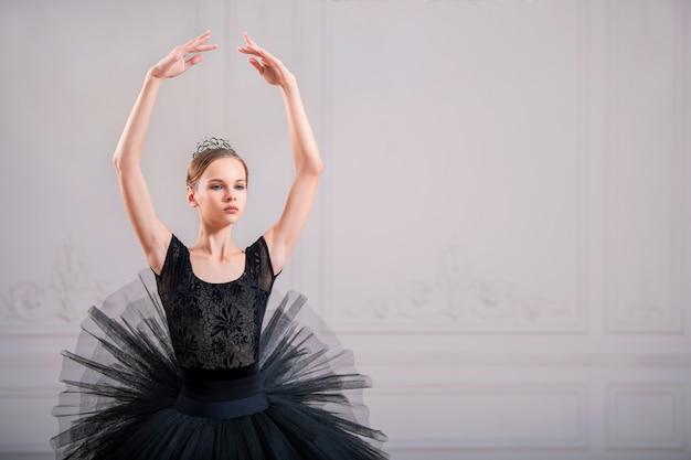 고전적인 위치에서 검은 투투를 입은 새로운 발레리나의 초상화