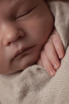 Портрет новорожденного ребенка, спящего в обмотке пальцами