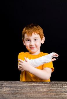 医療包帯で自分自身を包帯で包む軽傷の赤い髪の素敵な男の子の肖像画、自己治療と応急処置中に医療機器を持っている男の子、クローズアップ