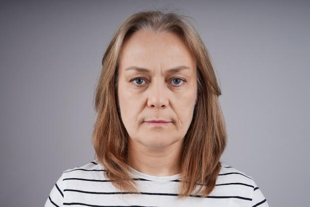 カメラを見ている縞模様のシャツを着た素敵な中年女性の肖像画