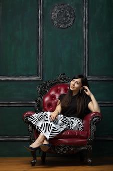 美しい高価な椅子に座っている素敵な笑顔の女性の肖像画