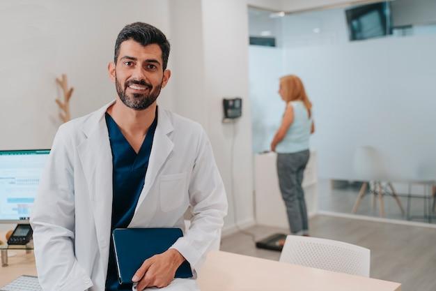 彼が彼のタブレット、メーター、リンゴで示されている彼のオフィスの栄養士の肖像画。そして背景には70代くらいの女性が自分の体重を量っています