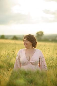 Портрет полной женщины в розовом платье. женщина стоит на зеленом пшеничном поле.