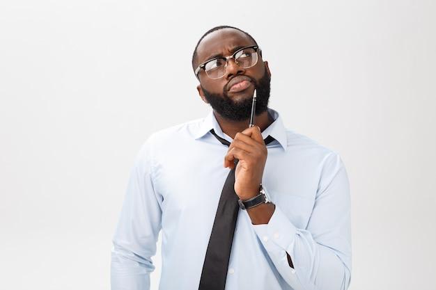 Портрет задумчивого афро-американского бизнесмена в сером костюме, думающего ручкой на лице