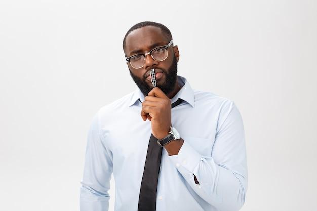 Портрет задумчивого афро-американского бизнесмена в сером костюме, думающего ручкой во рту