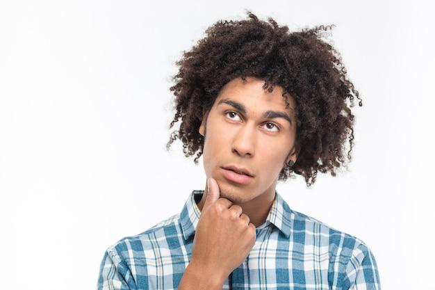 곱슬 머리를 가진 잠겨있는 아프리카 미국 남자의 초상화는 흰 벽에 고립 된 찾고