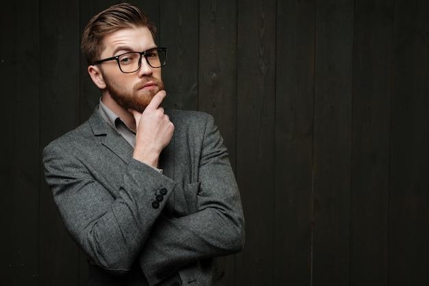 Портрет задумчивого бородатого бизнесмена в очках, смотрящего в камеру, изолированного на черном деревянном фоне