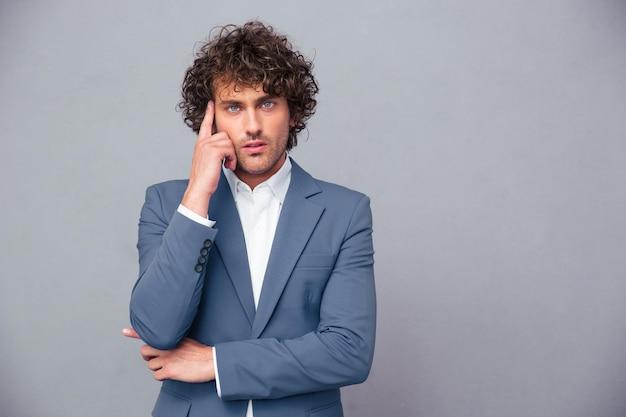 Портрет задумчивого бизнесмена, смотрящего на фронт через серую стену