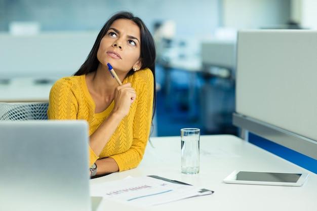 Портрет задумчивой бизнес-леди, сидящей на своем рабочем месте в офисе и смотрящей вверх