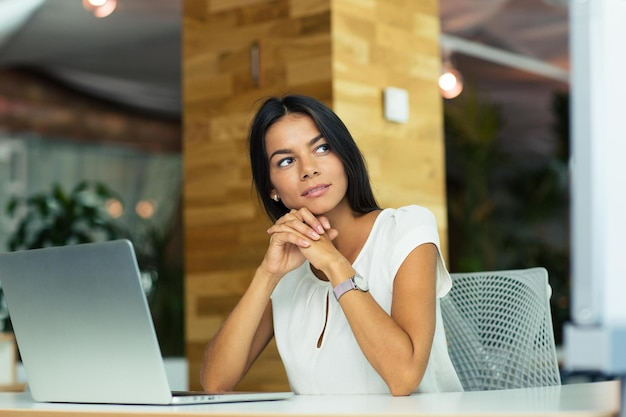 Портрет задумчивой бизнес-леди, сидящей за столом в офисе и смотрящей в сторону