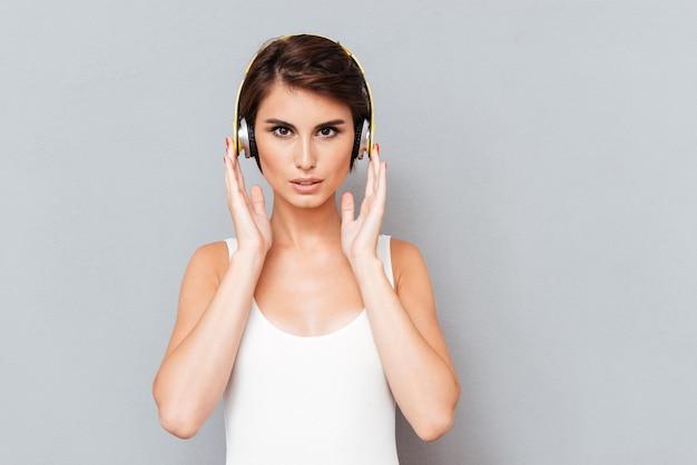 Портрет задумчивой сосредоточенной женщины, слушающей музыку в наушниках на сером фоне