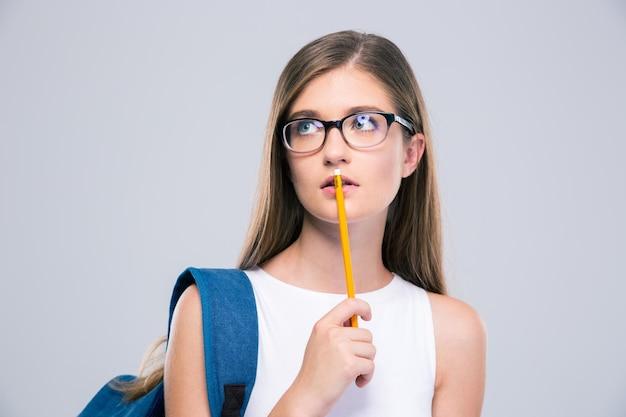 Портрет задумчивого женского подростка держа изолированный карандаш. глядя
