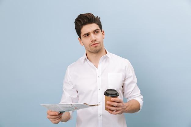 Портрет задумчивого красивого молодого человека, стоящего изолированно на синем и держащего чашку кофе на вынос