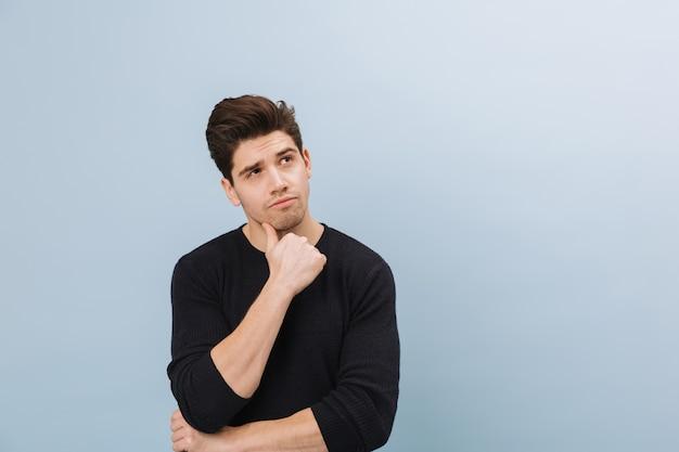 Портрет задумчивого красивого молодого человека, стоящего изолированно на синем
