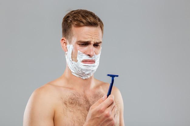 Портрет задумчивого мужчины, бреющегося над серой стеной