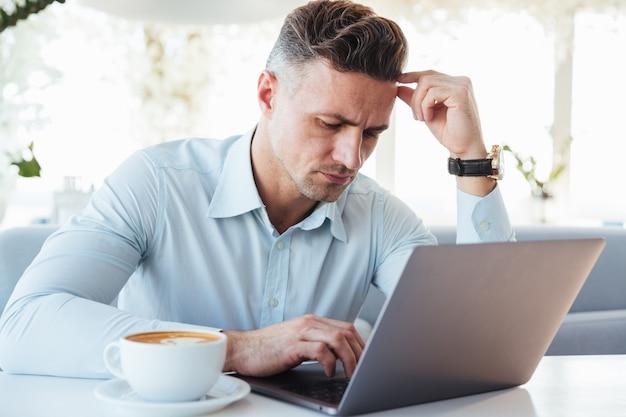 Портрет задумчивого зрелого человека, использующего ноутбук