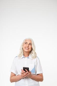 携帯電話を保持している物思いにふける成熟した女性の肖像画