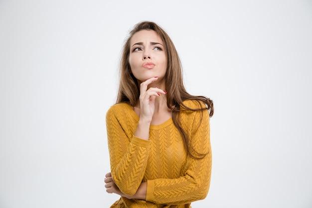 Портрет задумчивой женщины, стоящей изолированной на белом фоне
