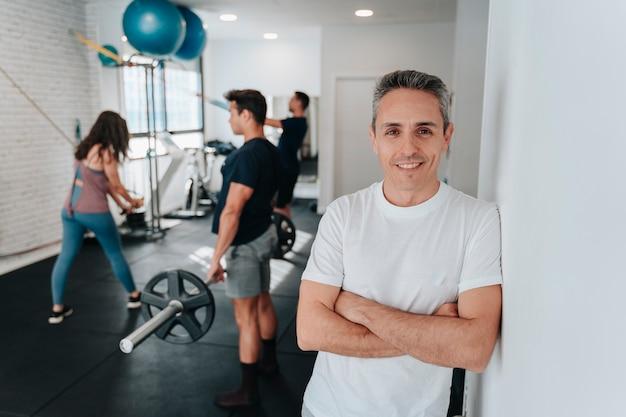 Портрет личного тренера и мальчиков, которых он тренирует, бегают, поднимают тяжести и делают упражнения для рук.