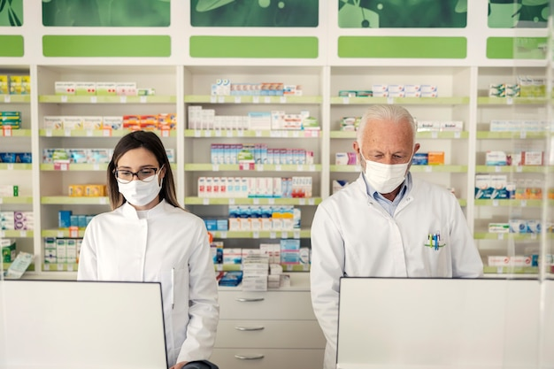Портрет фармацевта и вируса короны. пожилой фармацевт-мужчина и взрослая женщина-аптекарь стоят за прилавком в аптеке и продают лекарства. они носят униформу и маски для лица.