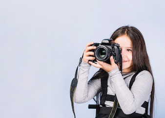 Portrait of a photographer covering her face with the camera against white backdrop