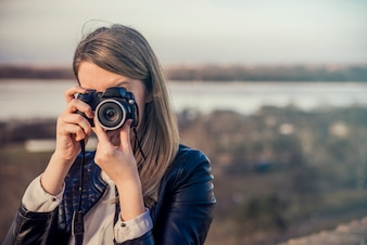 Portrait of a photographer covering her face with the camera. Ph