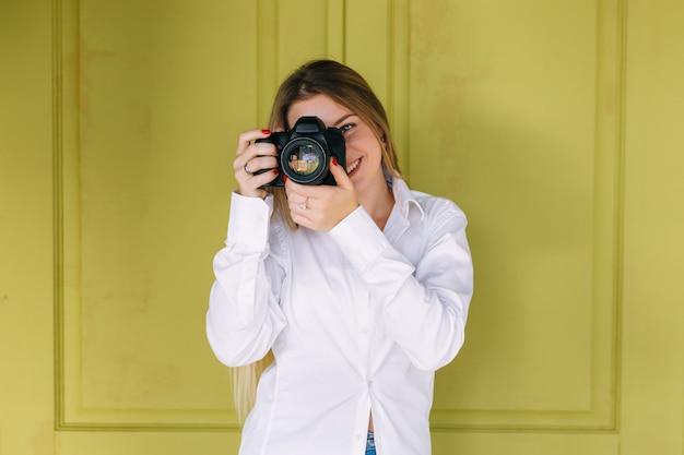 Портрет фотографа, закрывающего лицо фотоаппаратом