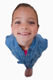 Portrait of a playful girl smiling at the camera against a white background